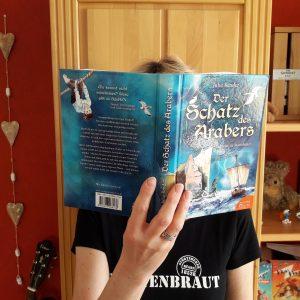 """Julie Bender versteckt sich hinter dem Buch """"Der Schatz des Arabers - Zeitreise zu Störtebeker"""""""