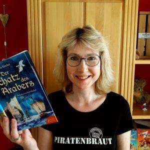 """Julie Bender sieht hinter dem Buch """"Der Schatz des Arabers - Zeitreise zu Störtebeker"""" hervor"""