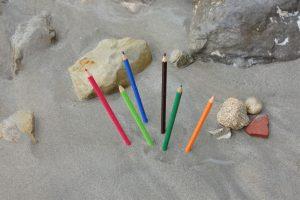 Sechs Buntstifte stecken am Wassersaum im Sand